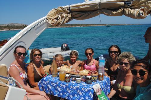 Gruppo di escursionisti mangia a bordo di un maxi gommone nel Golfo dell'Asinara
