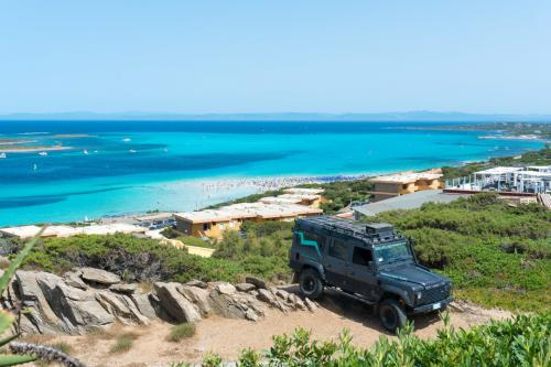 Off-road vehicle with La Pelosa beach in the background