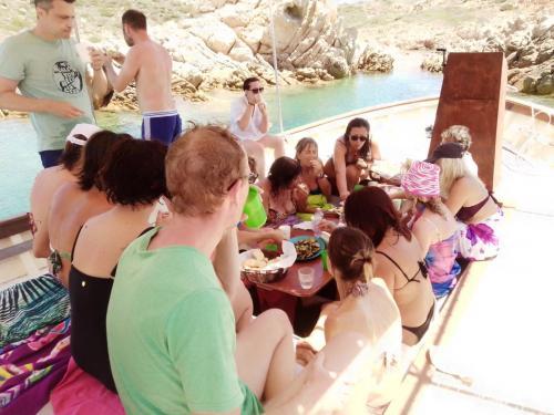 Gruppo di escursionisti pranzano a bordo di un gozzo in legno durante escursione alla Maddalena
