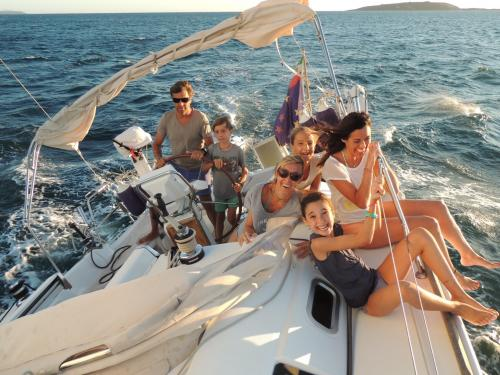 Family with children has fun aboard a sailing boat