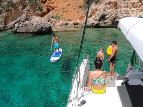 Boy on SUP and passengers on board a catamaran