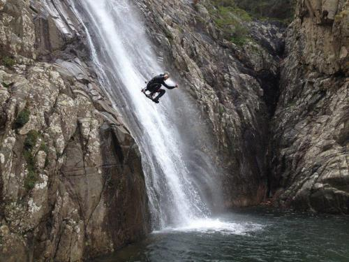 Hiker dives from the falls in Villacidro during a guided excursion