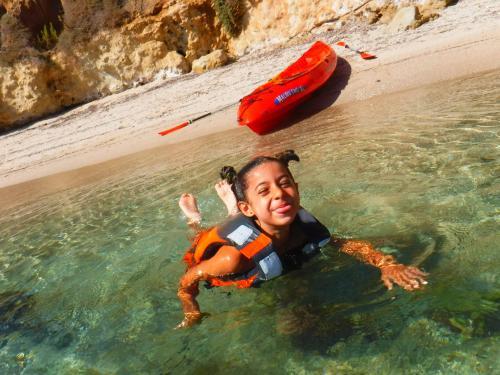 Niña nada en el mar de Balai durante una excursión en kayak
