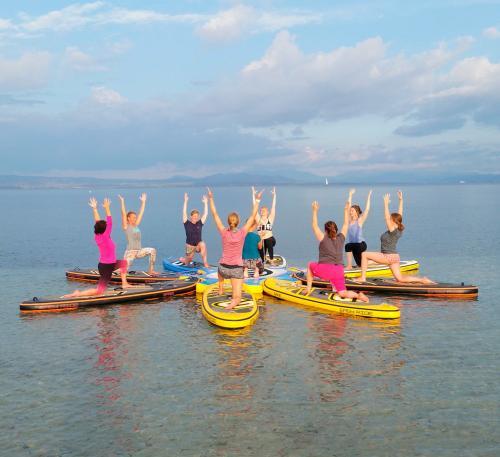 Eine Gruppe von Mädchen in SUP macht Übungen auf der Insel San Pietro