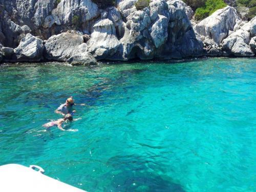Wanderer im kristallklaren Meer von Alghero