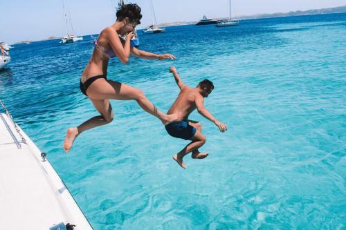 Boys jump from a catamaran