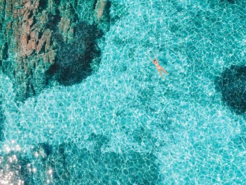 Girl swims in the crystal clear sea of the La Maddalena Archipelago
