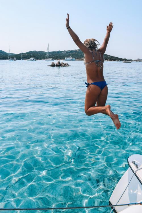 Girl dives from a catamaran