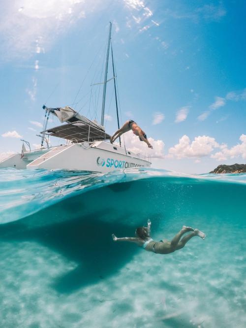 Garçon plonge depuis un catamaran