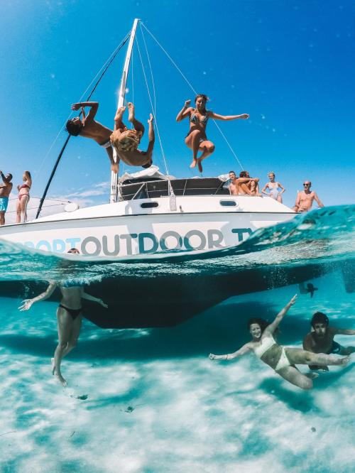 Group of friends aboard a catamaran dive and have fun