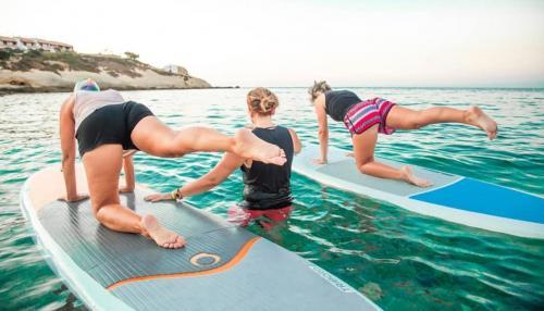 Ausbilder und Leute während des Pilates-Unterrichts auf dem SUP