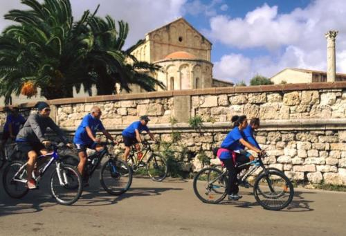 Group of hikers on bikes in front of Basilica of San Gavino