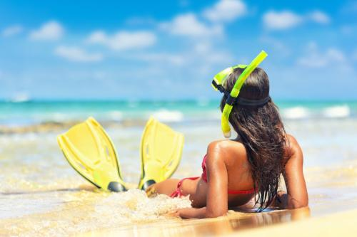 Girl at the beach with mask and flippers