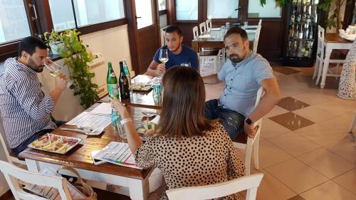 Tre persone assaggiano delle tipologie di vino sardo