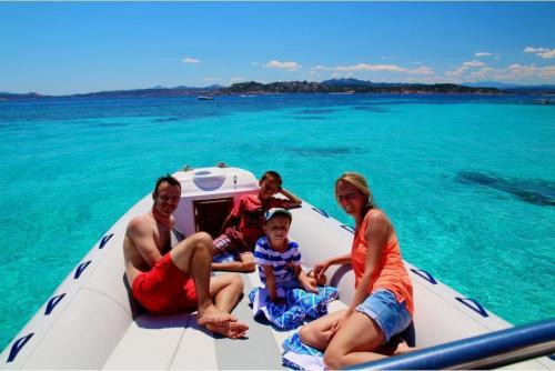 Familie an Bord eines Schlauchboots im Meer des La Maddalena Archipels