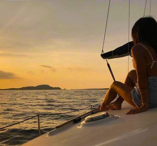 Mädchen an Bord eines Katamarans bei Sonnenuntergang