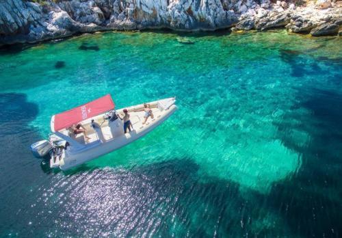 Embarcación neumática en el Golfo de Alghero y mar cristalino