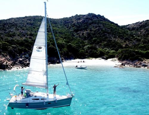 Sailboat reaches an island of the La Maddalena Archipelago
