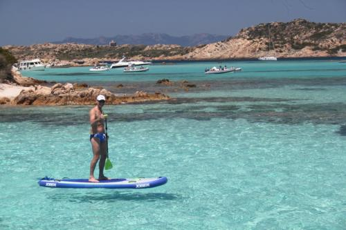 Boy uses the SUP in crystal clear waters