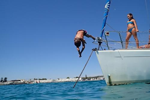 Bambino tuffa da una barca a vela