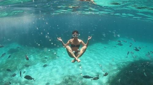 Girl snorkels in the crystal clear sea