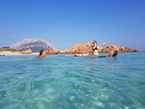 Girls swim in the crystal clear sea in front of Tavolara during a daily boat tour