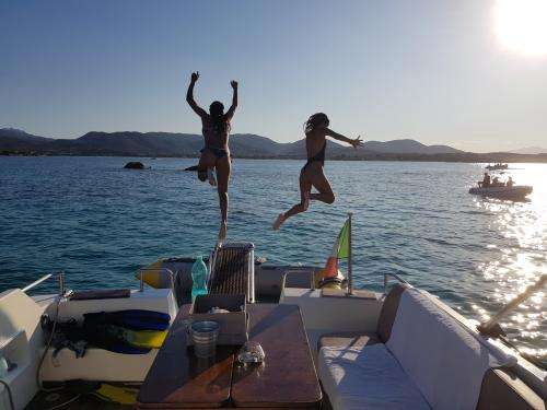 Boys jump off the boat at sunset