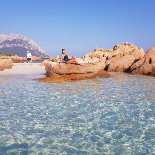 Girl relaxes on a beach in front of Tavolara