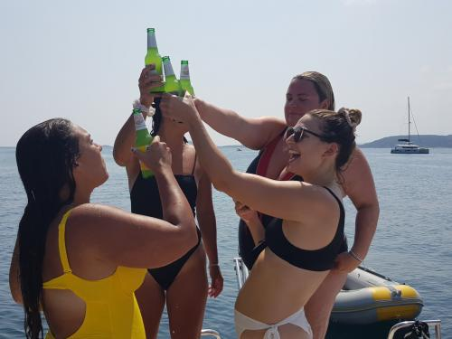 Girls aboard a boat make a toast with beer