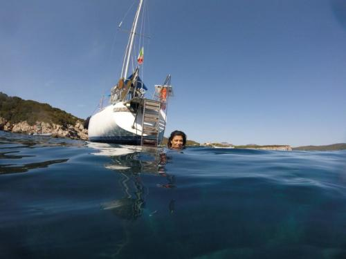 Girl swims after dive from the sailboat