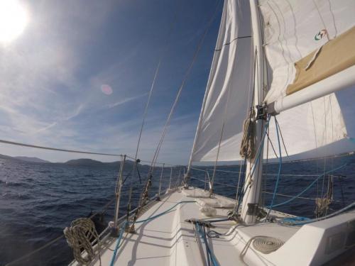 Sailboat sails in the sea of Alghero