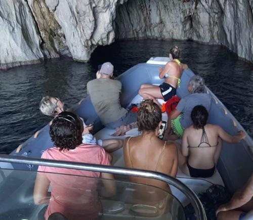 Gruppe von Wanderern an Bord eines Schlauchbootes in Masua