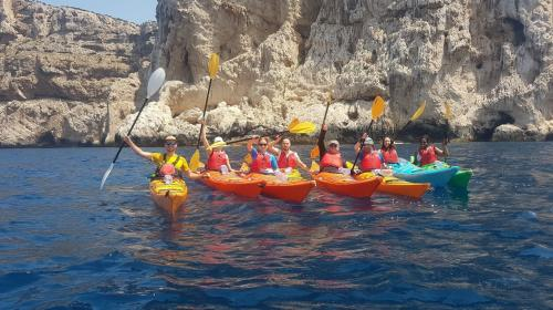 Group of people in a kayak to discover the coast of Alghero