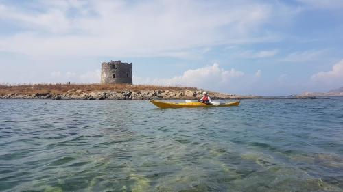 Tower in the coast of Alghero and hiker in a kayak