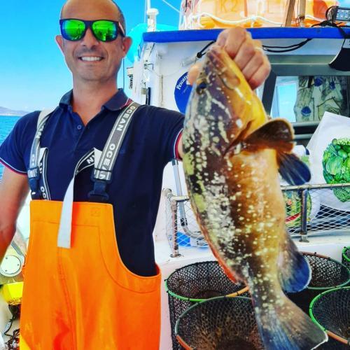 Kapitän mit frisch gefangenem Fisch