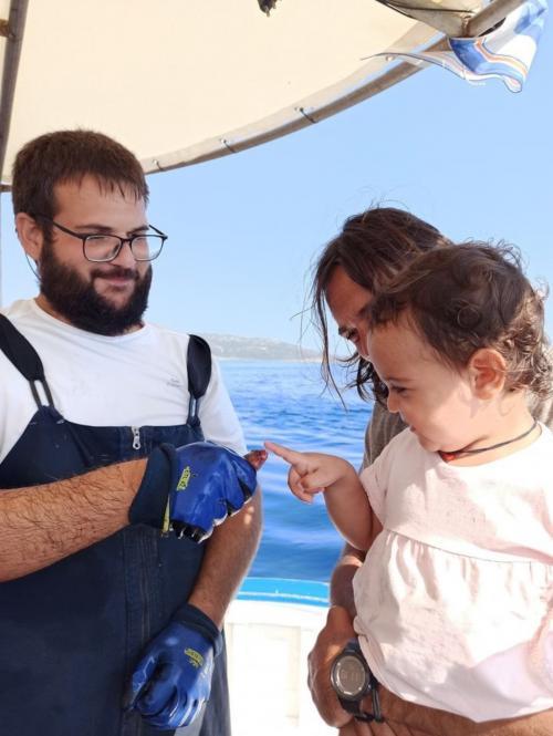 Kleines Mädchen berührt einen frisch gefangenen Fisch
