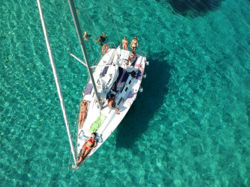 Segelboot und Passagiere im blauen Meer von Stintino