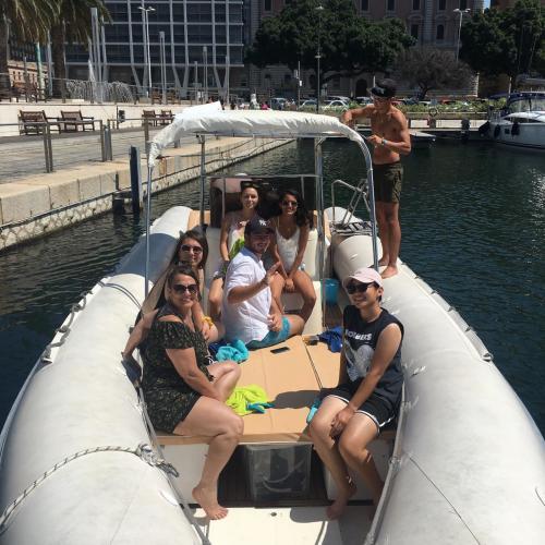 Passagiere an Bord eines Schlauchboots im Hafen von Cagliari