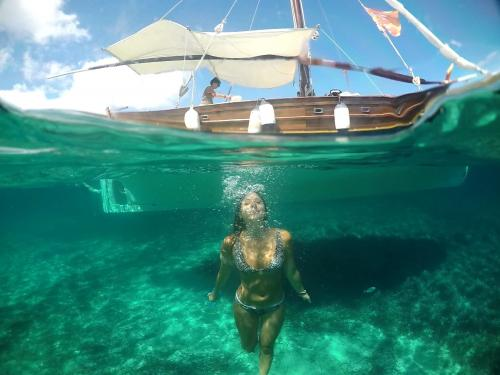 Girl snorkels during a day trip in a vintage sailing ship