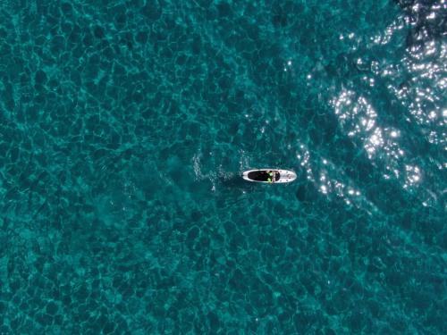 SUP person in the crystalline sea of the Gulf of Orosei