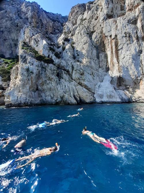 Wanderer schwimmen in Tavolara während Schlauchboot-Touren