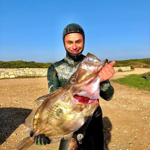 Wanderer mit frisch gefangenem Fisch bei einem Ausflug nach Porto Conte