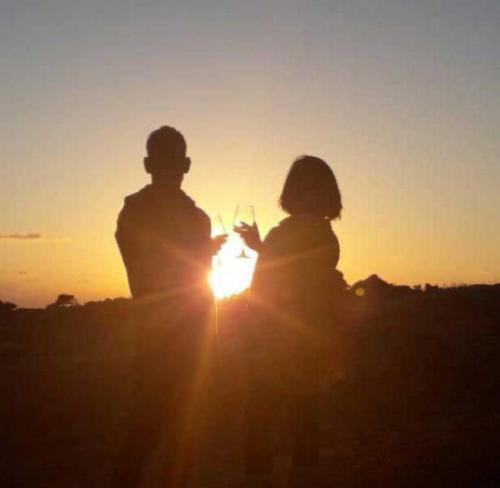 Couple makes aperitif with wine at sunset