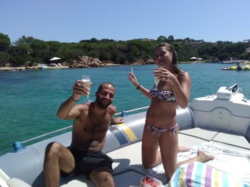 Couple of kids having an aperitif on board an inflatable boat