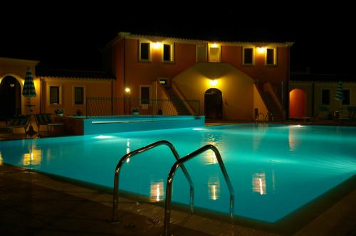 Piscina de noche en una Residencia en Arbatax