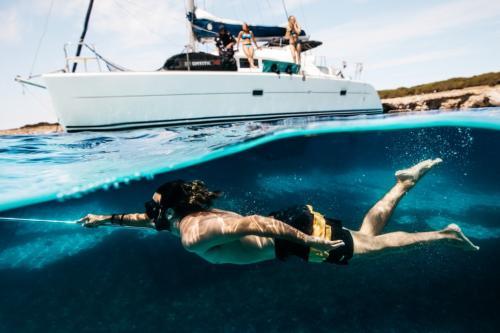 Ragazzo nuota nell'Arcipelago di La Maddalena con catamarano sullo sfondo