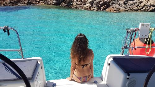 Girl sitting on the catamaran docked in the islets of the La Maddalena Archipelago