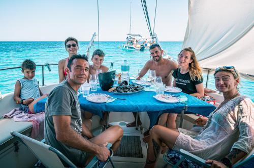 Group of passengers during lunch on board a sailing boat in the waters of Asinara