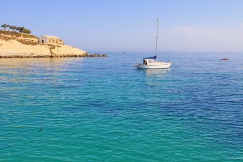Barca a vela nella baia di Balai a Porto Torres
