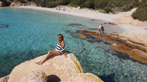Girl admires the crystal clear sea of the La Maddalena Archipelago